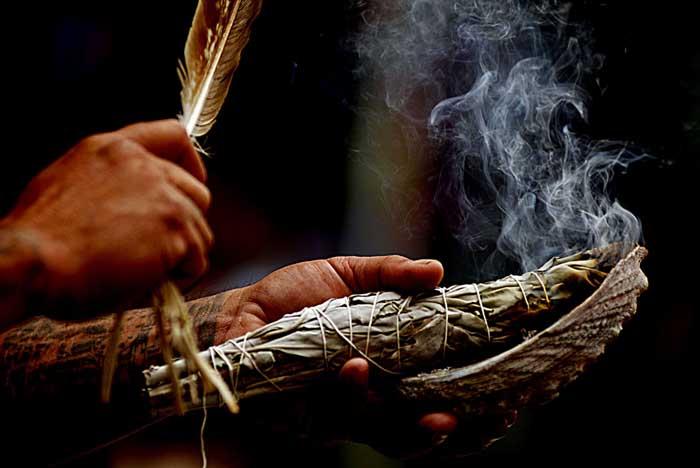 Pratique d'un smudge, main avec plume d'oiseau, sauge qui fume et coquillage
